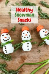 "Three snowman snacks on a cutting board next to each other with words ""healthy snowman snacks"""