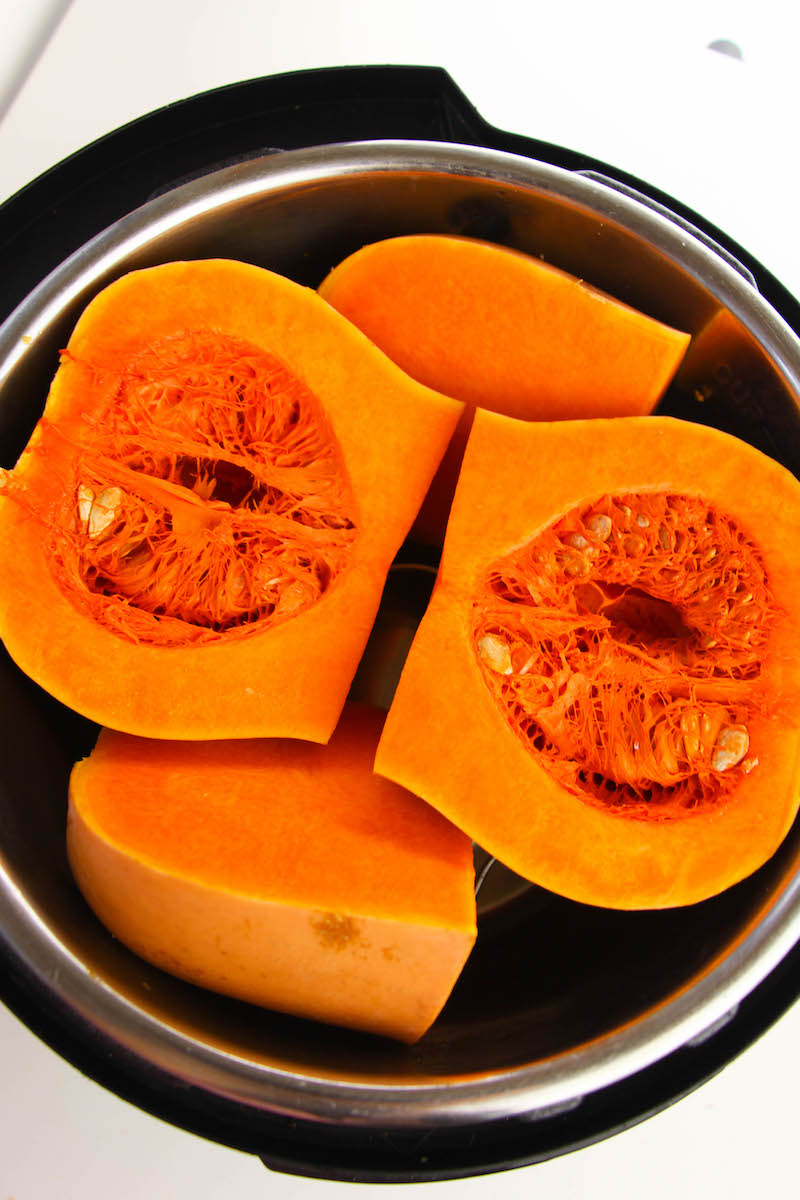 An instant pot filled with quartered butternut squash.