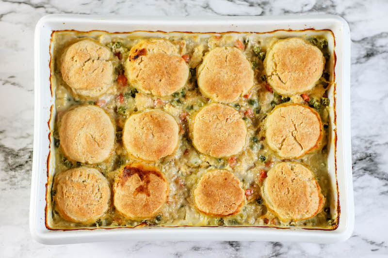 Chicken pot pie with biscuits in white baking dish.