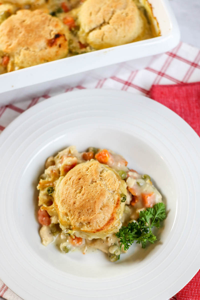 A serving of chicken pot pie on a white plate next to a baking dish of chicken pot pie.