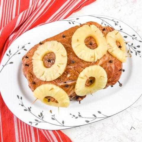 Ham covered in pineapple on white platter.