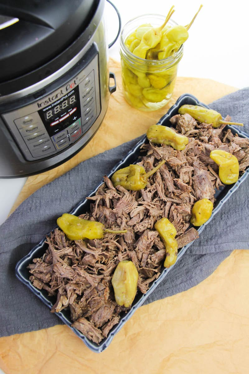 Instant pot, plate of Italian beef, and jar of peppers.