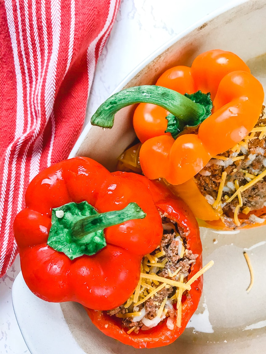 A red and orange stuffed pepper next to each other in a serving dish.