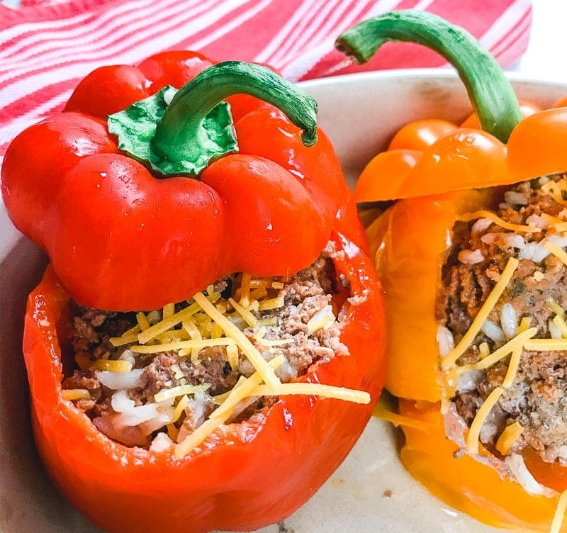 A red bell pepper stuffed with cooked ground beef and topped with cheese.