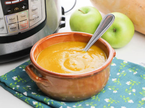 butternut squash soup in a red ceramic bowl in front of instant pot.