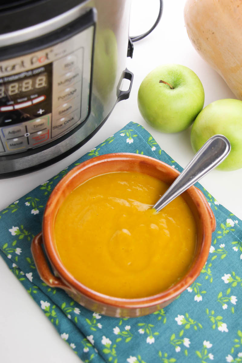 Overhead shot of butternut squash soup in bowl next to butternut squash, apples, and instant pot.