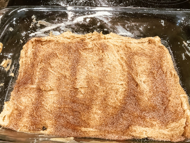 Snickerdoodle bar dough sprinkled with cinnamon sugar.