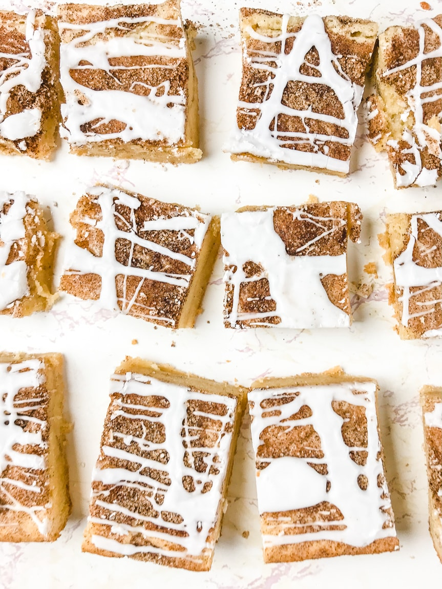 Snickerdoodle bars cut into squares and drizzled with icing.