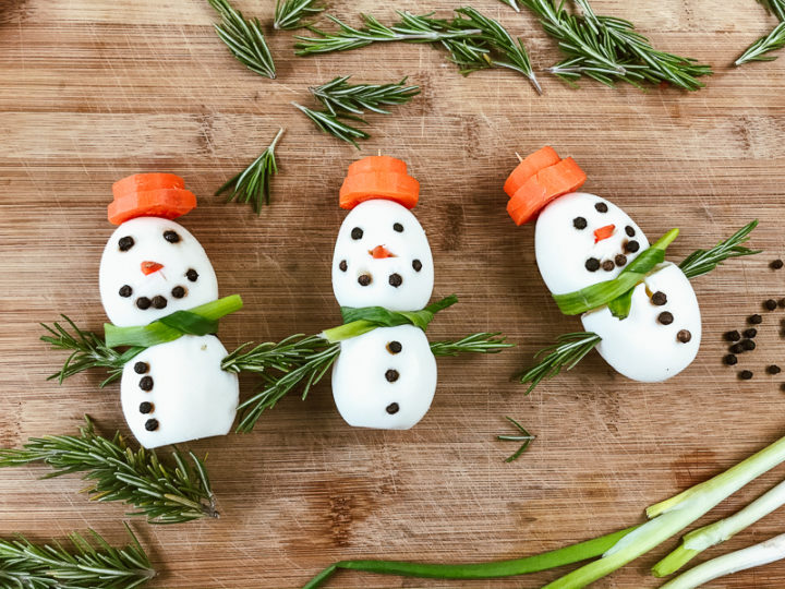 Three hard-boiled-egg snowmen on a wooden cutting board