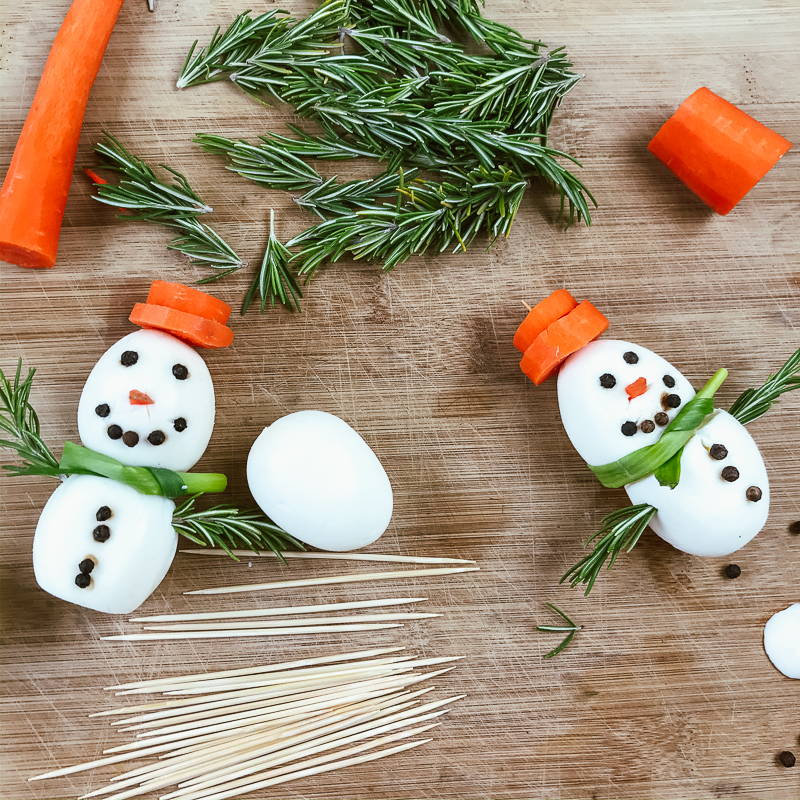 Two egg snowmen next to wooden skewers, carrots, and rosemary.