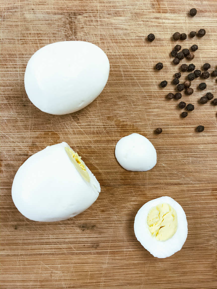 Hard boiled eggs with the bottoms sliced off to make them flat.