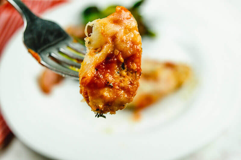 Close up of bite of chicken parmesan on a fork.
