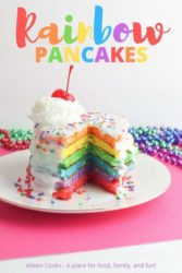 A tall stack of rainbow colored pancakes with whipped cream and cherry on top.