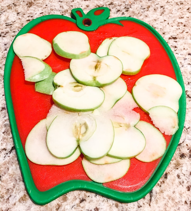 Apples sliced thinly on an apple shaped cutting board.