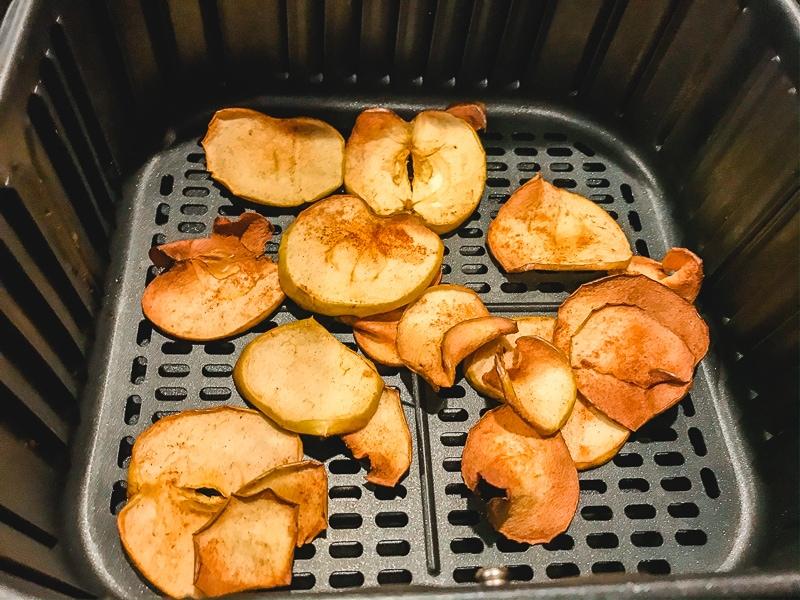 Cooked apple chips inside air fryer basket.