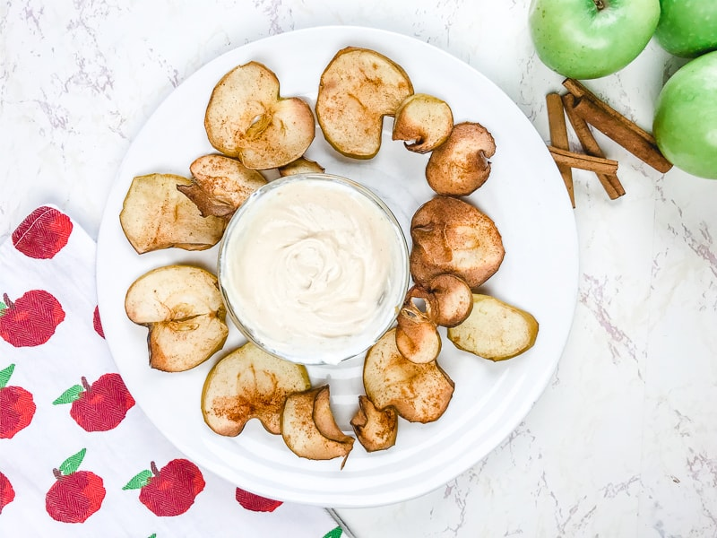 A white plate filled with apple chips arranged around a creamy beige dip.