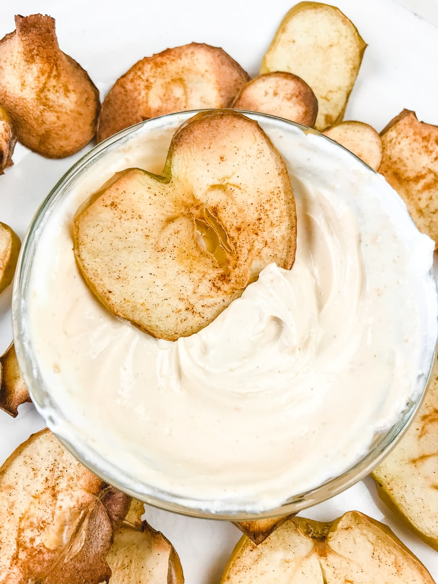 An apple chip dipped into creamy peanut butter dip.