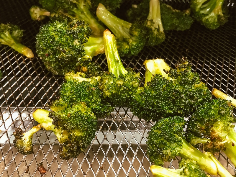 Freshly air fried broccoli on tray.