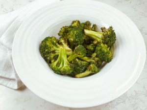 Air fryied broccoli in white rimmed bowl.