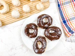 A white plate of chocolate glazed donuts next to a cutting board filled with glazed donuts and donut holes.