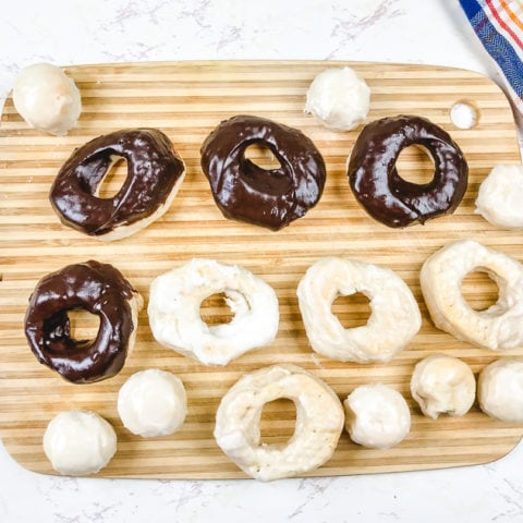 A cutting board filled with chocolate donuts, glazed donuts, and donut holes.