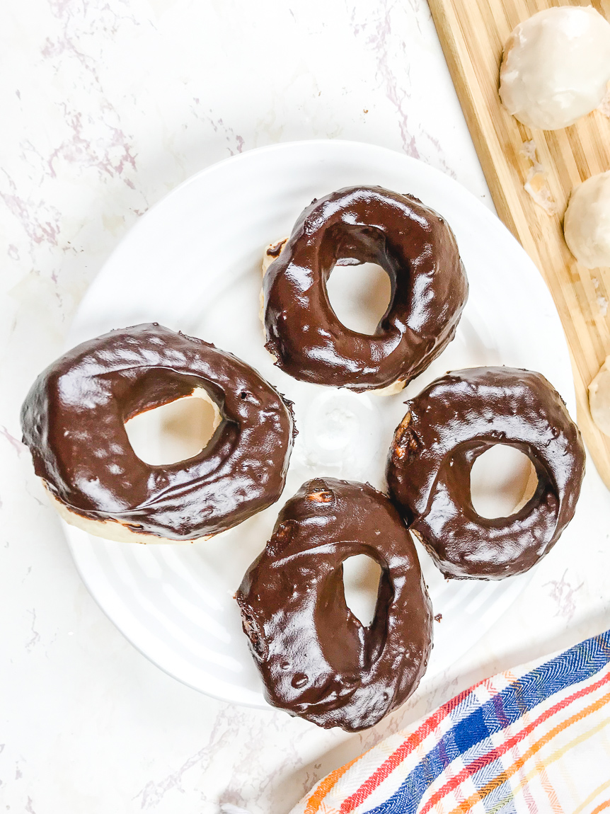 A white plate with four chocolate glazed donuts.