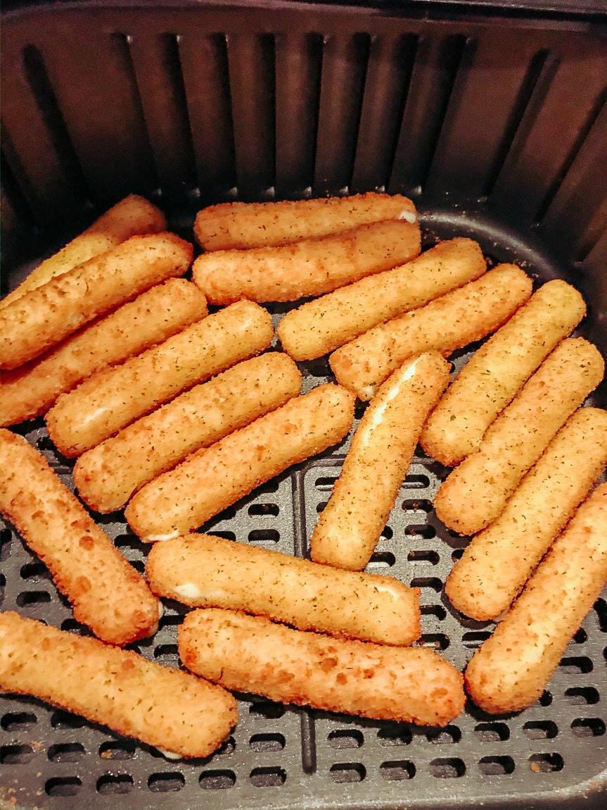 Breaded mozzeralla sticks inside air fryer.