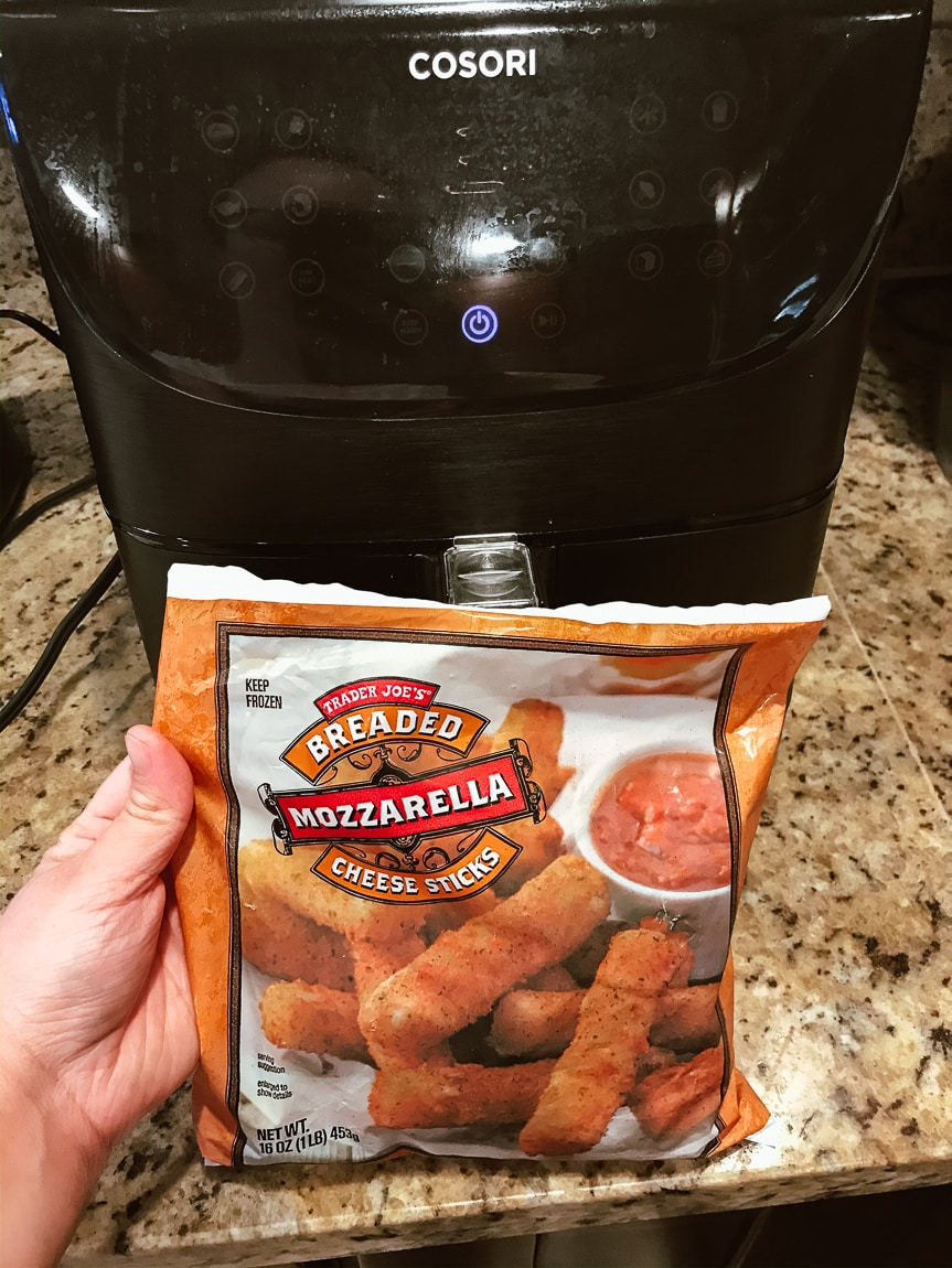 Bag of mozzarella sticks being held in front of black air fryer.