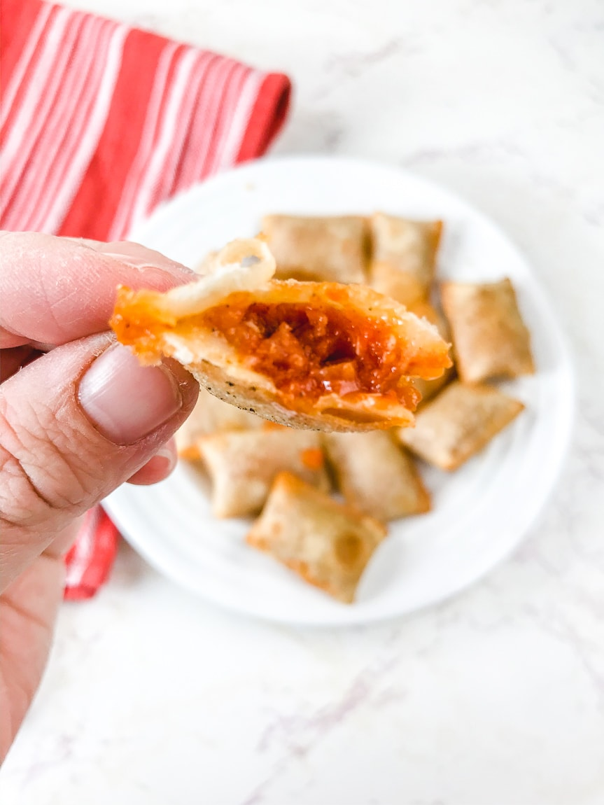 A hand holding a pizza roll with a bite out of it.