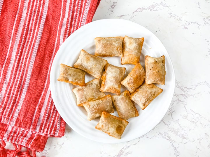 A white plate with air fried pizza rolls.