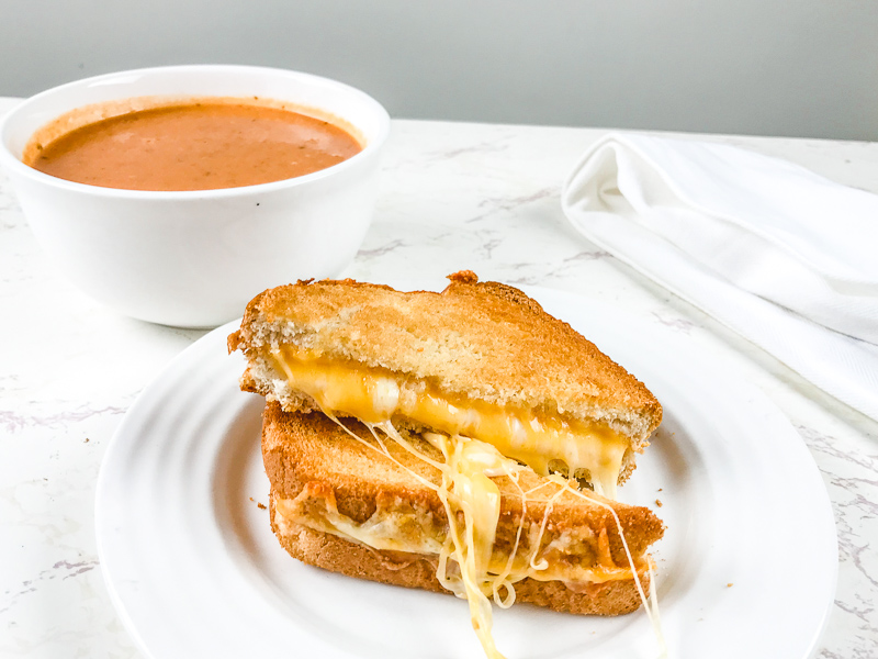 A grilled cheese on a white plate next to a bowl of tomato soup.