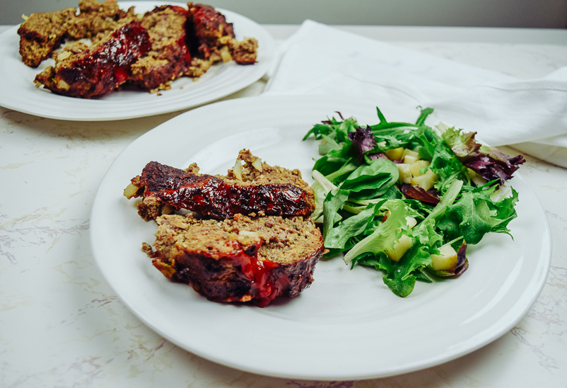 Plate of meatloaf and salad in front of platter of air fried meatloaf.