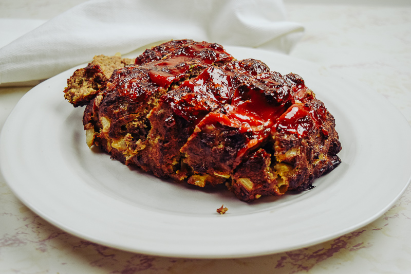 Cooked meatloaf on a white plate.