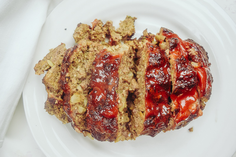 Sliced meatloaf topped with ketchup on a white plate.