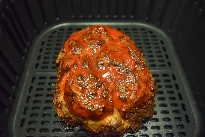 Cooked meatloaf with ketchup brushed on top inside air fryer basket.