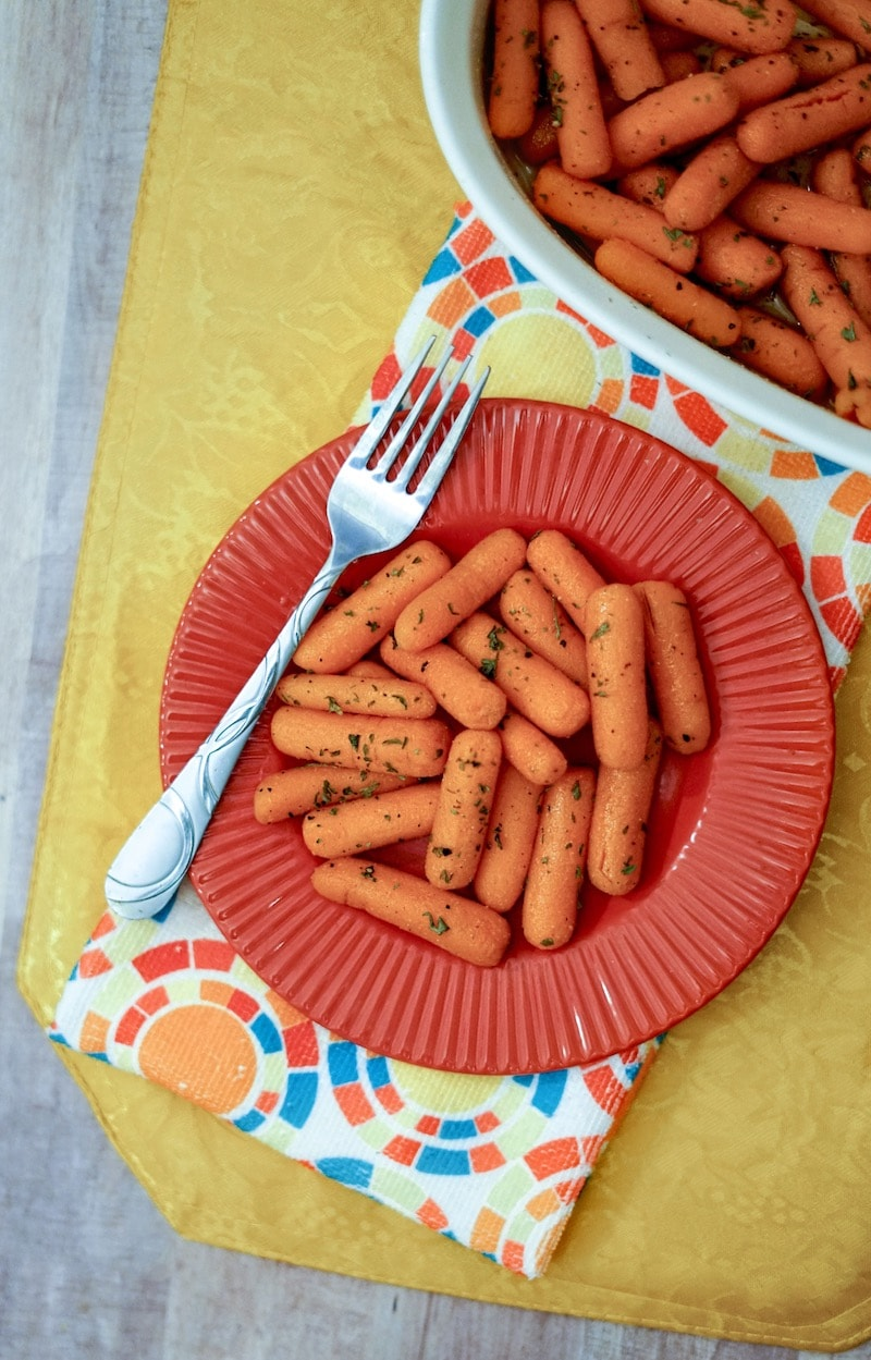 A plate of roasted buttered carrots topped with parsley.