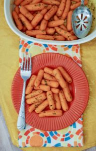 A plate of carrots below a baking dish of buttered carrots with a spoon inside the dish.