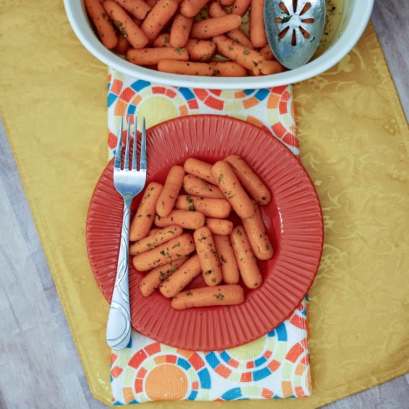 A red dish filled with buttered carrots on top of of a floral napkin and yellow placemat.