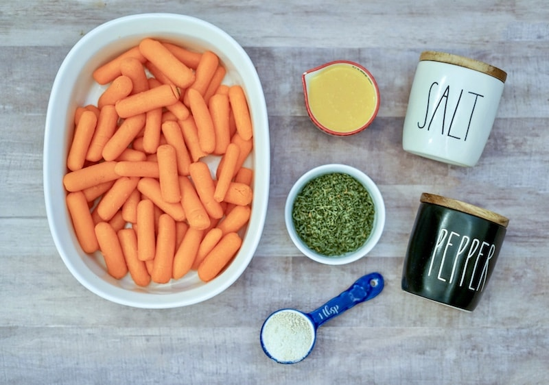 Baby carrots in baking dish next to ingredients for garlic butter.