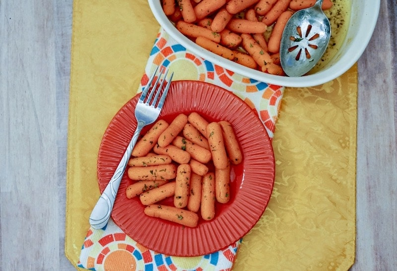 A red plate filled with buttered carrots and a fork propped on top.