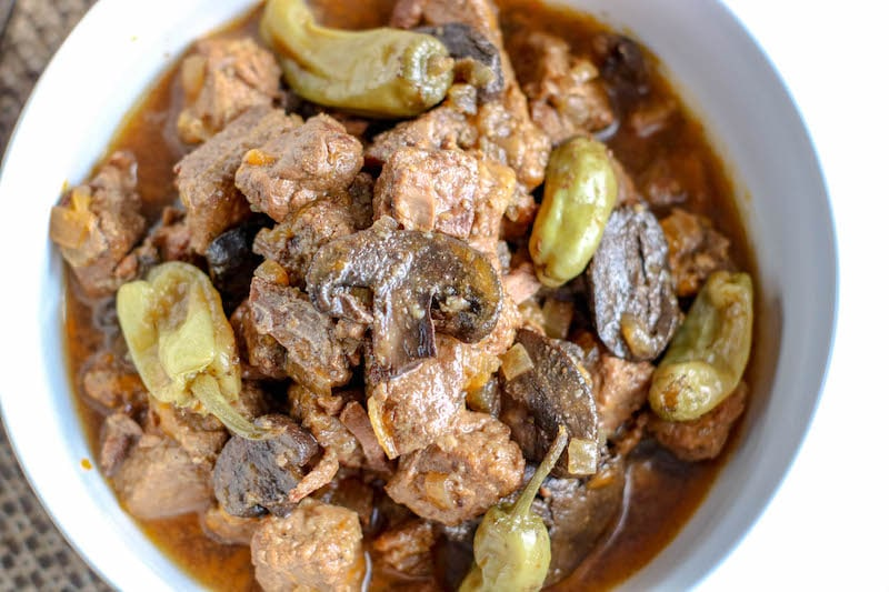 Crockpot beef tips with gravy and mushrooms in white bowl.
