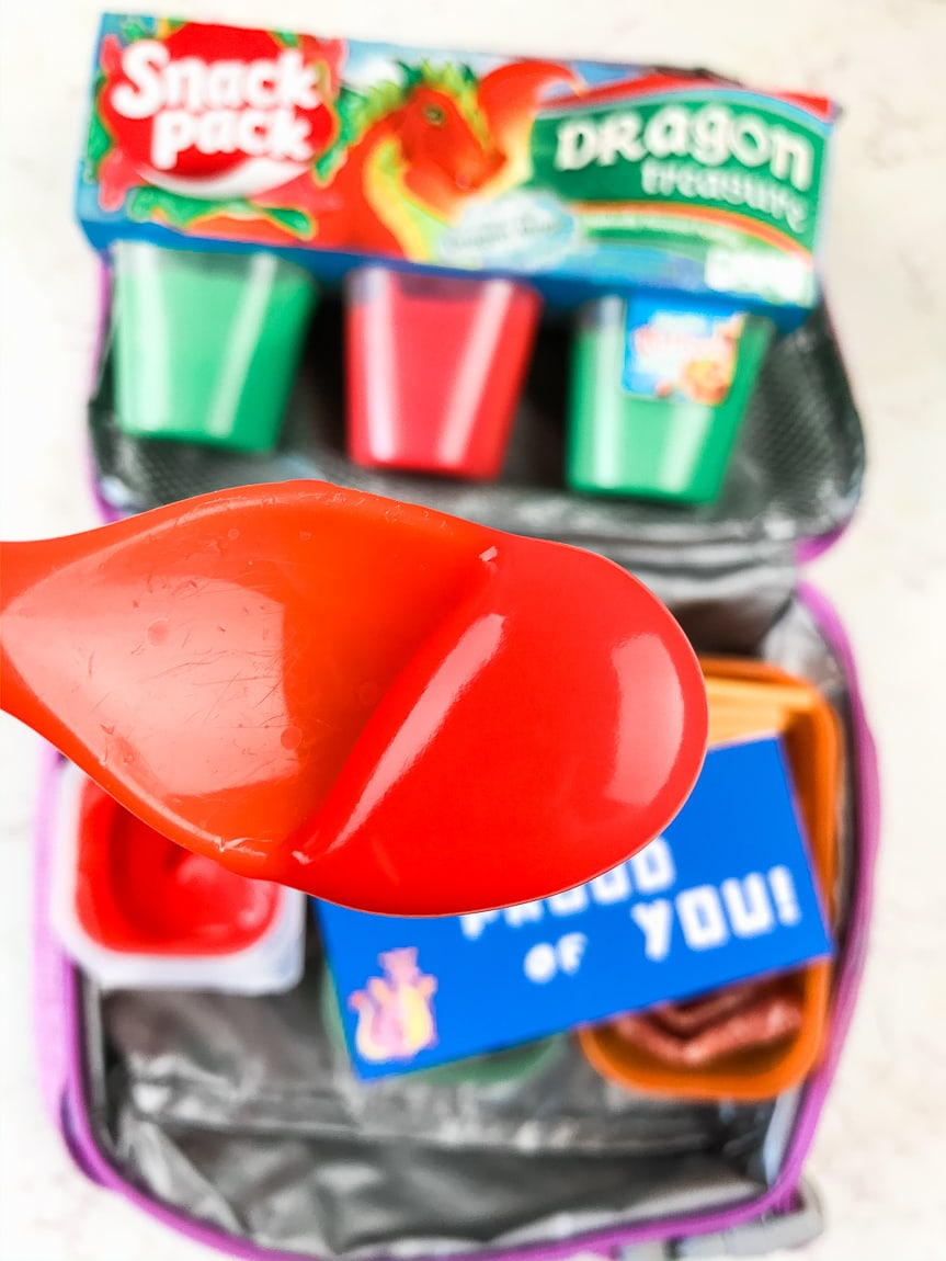 Spoonful of red snack pack above lunchbox.
