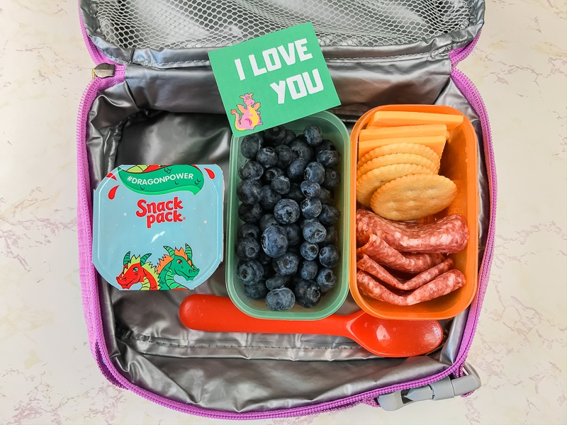 "Lunchbox with salami, cheese, blueberries, snack pack, and lunch note that says ""I love you""."