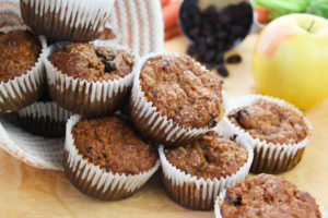 A pile of morning glory muffins spilling out of a bowl with an apple and raisons in the background.