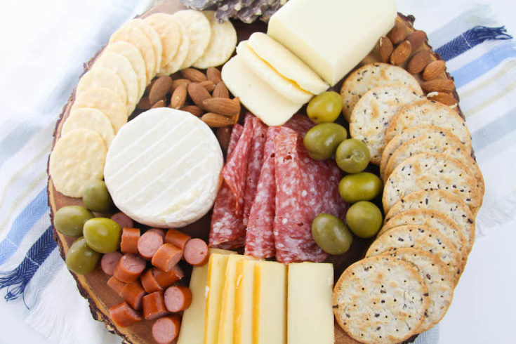 Learn how to make a charcuterie board that's both beautiful and functional, filled with meats, cheese, and crackers. We are showing you exactly what to put on your charcuterie board and how to arrange it!