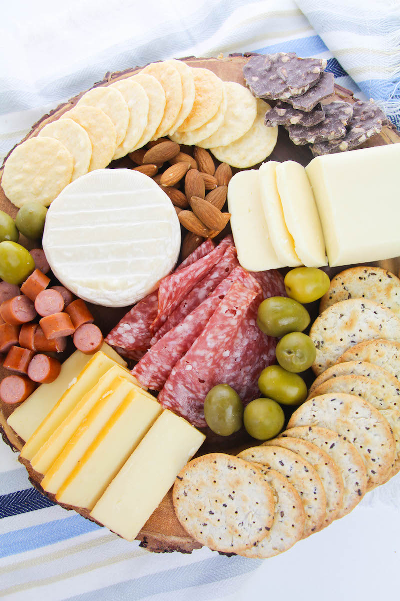A wood round filled with meats, cheese, crackers, almonds, and olives.
