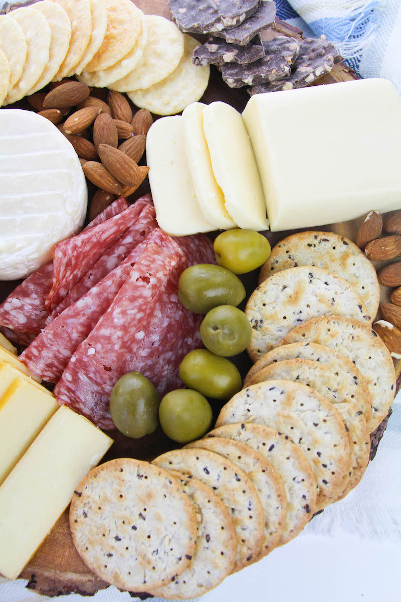 Olives and almonds on charcuterie board.