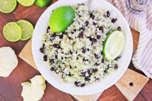 Over head shot of instant to cauliflower rice in a white dish topped with lime wedges.