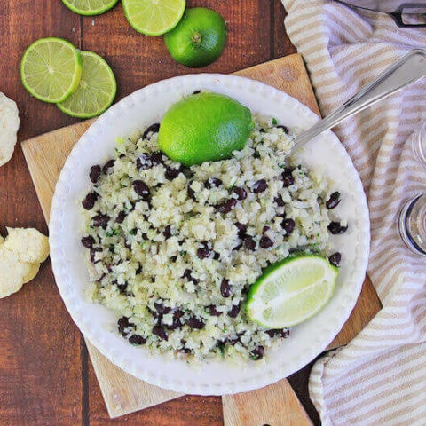 White dish of cauliflower rice next to cauliflower florets, limes, and striped towels.