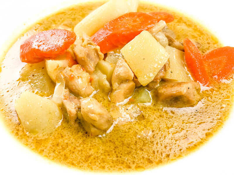Close up of chicken curry in white bowl.